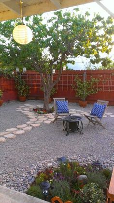 Drought tolerant gravel garden.  Gravel with fruit trees. Like the larger river rock around garden bed.  The reddish fence is thecsame color as our deck and hot tub.