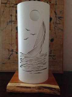 Perfect lighting solution for beach and marine themed decor.A sleek sailboat catching the wind at sunset.Made from creamy piping ,when it throws up a spectacular silhouette . The table lamp is 40 cm tall x18 cm diameter, a solid pine base,and CE certified electrics. Cut on the round,there