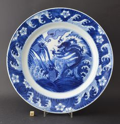 A fine Kangxi blue and white porcelain Dragon and Carp dish c.1700. Painted in rich vibrant tones of cobalt blue with dramatic version of this design, a large sinewy dragon thrusts its self up through crashing waves below it a carp leaps from the foaming sea. To the left is another carp on the edge of a wave with a thought bubble filled with a slender dragon. The border with crashing waves and prunus flower-heads.