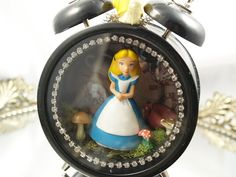 Not into the Alice theme but I love the idea of repurposing an alarm clock into art.
