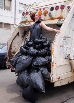 A model is displaying suit attached with wastage bags in garbage truck, Stinky art...Definitely non-biodegradable!!!