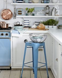The clean metro tile backdrop and rustic white wood cupboards are turned positively coastal with a charming collection of sea-toned kitchenalia