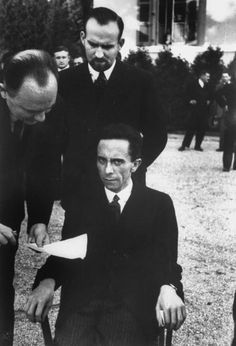 """Hitler's Minister of Propaganda Joseph Goebbels glowers at photographer Alfred Eisenstaedt in the garden of the Carlton Hotel during a League of Nations conference, Geneva, September 1933.Goebbels smiled at him until he learned that Eisenstaedt was Jewish - a moment Eisenstaedt captured in this photo. Suddenly, """"he looked at me with hateful eyes and waited for me to wither,"""" the photographer recalled."""