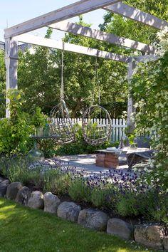 Perfetto spazio relax immerso nel verde con il pergolato in legno bianco che sostiene due comode poltrone sospese - idee progettazione giardino rustico