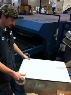Great shot of Kyle changing his platen tape.  We use this tape to keep our chemical usage down as we can clean the platens quicker and easier.  To top, we use a liquid glue instead of spray adhesive.  Sustainability.  www.visualimp.com