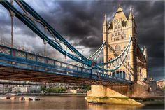 The iconic London Tower bridge captures direct sunlight against a backdrop of thick grey clouds, for a compelling visual effect.