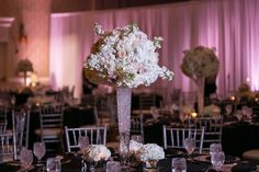 Tall, White and Blush Pink Wedding Centerpieces with Sparkle Accents and Uplighting | Black Table Linens with Silver Chiavari Chairs, Blush Pink Uplighting at Vinoy Renaissance Wedding Venue in St. Petersburg Florida | Photo by Carrie Wildes Photography