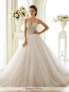 Tulle ball gown with sweetheart neckline, rich crystal hand-beaded embroidery adorns bodice, back corset, sparkling gathered full skirt with chapel train.