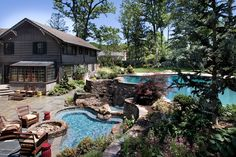 Do you have a yard elevated above the home? Landscape designers love a yard like this!  The topography allows for different levels of entertaining, such as with this water feature that connects the upper-level pool with a lower spa.