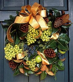Wonderful idea for an Autumn Equinox wreath... faux grapes, magnolia leaves, pine cones and lemons...