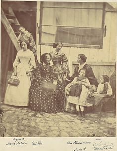 [Group Portrait of Four Women and Three Children]- child on chair does not appear to have any legs!