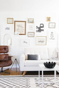 Minimalist living space with an eclectic gallery wall, a white sofa, a leather chair, and a Morrocean rug