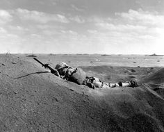 Death of a Marine: A US Marine lies on the black sands of Iwo Jima, shot trough the head by a Japanese sniper, Feb 19, 1945, against the dramatic backdrop of the invasion fleet that made the US landings possible. The bullet hole is clearly visible on the KIA's helmet.