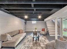 An unfinished basement, with its concrete floor and exposed joists, may seem dreary and cold. But in reality it is an enormous blank canvas just waiting for your inspired ideas and artistic vision. The fact is, you don't really need niceties like drywall and recessed lighting to create an inviting space.  Before you begin, do what you need to do to make sure the space is dry and clean. Fix any water issues and apply waterproofing if necessary. Unfinished concrete flooring will produce fine…