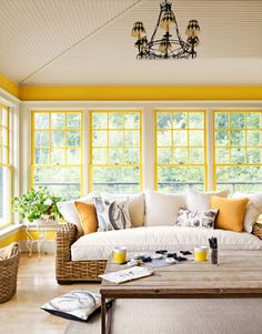 "Bright walls (Pratt & Lambert's Premium Yellow) and a rattan Pottery Barn sofa make sure that her ""winter porch"" always seems summery. A rough-hewn Sundance coffee table and nature-themed Design Legacy throw pillows enhance the room's laid-back vibe."