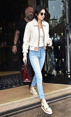 Kendall Jenner wears a tank top, shearling jacket, vintage jeans, platform oxfords, and a burgundy tote bag
