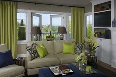 Fun green & blue living room design with gray walls paint color, French door, green curtains window panels, tan linen sofa & chairs, blue square velvet ottoman, silver garden stool, green & blue pillows and white built-ins.