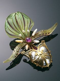 An Art Nouveau brooch, by Georges Fouquet. Fouquet exhibited this orchid brooch, designed by principal designer Charles Desrosiers, at the Salon des Artistes Français in 1898. The piece is based on a fully modelled paphiopedilum lawrenceanum orchid, with delicate plique-à-jour enamel work and a large central baroque pearl.