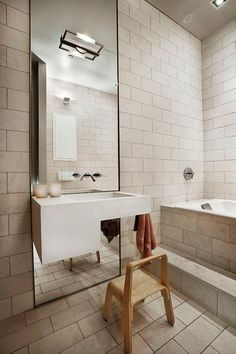Contemporary bathroom features beige brick tiled wall lined with an asymmetrical sink vanity mounted on a full length mirror alongside a blond wood stool next to steps to a tiled tub.