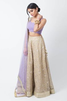 Karishma-holiCHIC. A gold net lengha with lavender detailing throughout. Blouse features laser cut layers, topped with a sheer embroidered matching dupatta. #holiCHIC #lehenga #lavender
