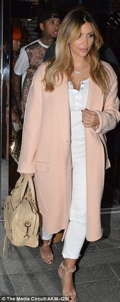 She's back: Kim continues to ease her way back into the spotlight but covered up her post-baby body in a long pink coat during dinner with K...