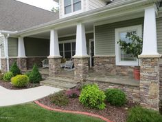 beautiful front porch made of stone with white pillars