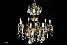 This heavy gilded Italian chandelier has 8 lights. french style and tear cut crystal drops hang all over the chandeliers. Icicle cut crystal drops hang on the outside arms of the chandelier. A central cut crystal ball is hanging on the bottom of the chandelier over a beaded wire