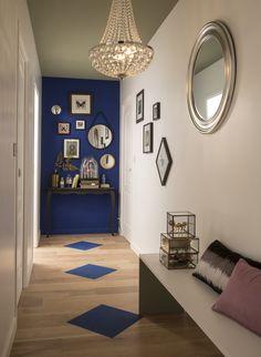 Le couloir peut aussi être conçu comme un minisalon. Un bel aplat de couleur sombre, en contraste avec des murs blancs, apporte profondeur et intimité. La couleur est reprise en écho au sol, comme un tapis. La belle suspension centrale offre un éclairage chaleureux. Une ou deux pièces de mobilier (banc, fauteuil, console…) habillent l'espace.   #leroymerlin #ideedeco #madecoamoi #couloir #lustre #suspension #baroque #bleu #blue #deco