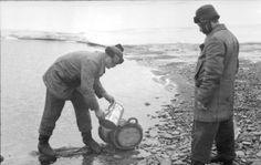 September 1943 - Rußland-Nord, Eismeer.- Zwei U-Boot-Besatzungsmitglieder füllen Wasser in ein Fass