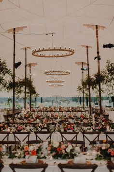 This cozy tent reception features long tables, colorful florals, and rustic chairs | Image by Cody & Allison Photography