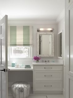 Elegant bathroom with silver Moroccan pouf tucked under a floating dressing table below a sunny window dressed with a white and jade green striped roman shade which accents with dressing table decor. Makeup Vanity Furniture, Bathroom With Makeup Vanity, Bathroom Vanity Designs, Small Bathroom Vanities, Small Vanity, Bathroom Renos, Bathroom Cabinets, Master Bathroom, Wood Cabinets