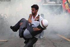 Un participante en las protestas lleva a un oficial herido a resguardo. Sao Paulo, Brasil, 2012.