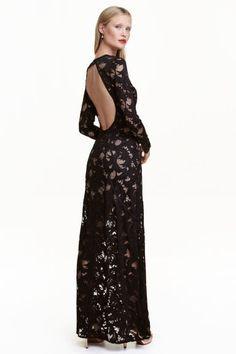 Robe longue en dentelle: Robe longue et ajustée en dentelle ajourée avec rubans appliqués. Modèle avec partie ouverte dans le dos et boutons sur la nuque. Manches longues terminées par bord à cru. Doublure contrastante.