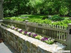 Wood fence with picket on stone wall