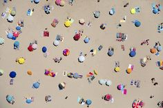 Umbrellas dot the beach like a cheery graphic pattern in Lisbon.