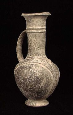 A CHOICE PHOENICIAN 'BIL-BIL', ca. 1200-900 BC. The classic Phoenician vessel with spherical body on everted ring base with high neck with everted rim, a single strap handle looping gracefully from the shoulder to the neck, the body ornamented with curving ridges.