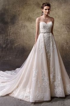 Enzoani Lucie Sheath wedding dress in chantilly lace with strapless sweetheart neckline. Features lace appliques throughout, detachable tulle overskirt with jewelled band at waist, and scalloped trim at hem. Wedding dress from Enzoani. Category: Wedding…
