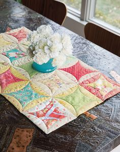 This quilt-as-you-go project features the peek a boo style quilt block in springy, modern fabrics. Learn how to make this table runner in a free video tutorial.