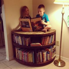 Up-cycled corner bookcase. Made with a recycled wire spool.  Cut to fit the corner, sanded, and stained.  Used shop wheels underneath (kept the bolts from damaging the floor, and also were just enough to move it, but not so movable to cause a danger).  Insert books!