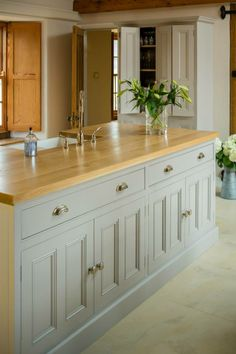 To create seamless uniformity, all the units were made from Quebec Yellow Timber, hand-painted in Farrow & Ball 'Dove Tale'. White bronze knobs and cup handles give that extra polished look. All the worktops are made from solid English Oak to add warmth and contrast against the cool, muted finish of the cabinets.