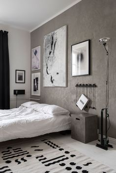 Bedroom with grey wall and large artwork in a monochrome Helsinki apartment