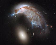 "The ""Porpoise"" galaxy (top) is in the process of colliding with a huge elliptical galaxy (bottom). It is being warped by the gravitational interaction between the two galaxies. The collision takes place in extreme slow-motion, it may take billions of years for the galaxies to fuse. Colliding galaxies produce the conditions for the creation of new stars, areas of star formation glow bright blue.    Image Credit: NASA, ESA, and The Hubble Heritage Team (STSci/AURA)"