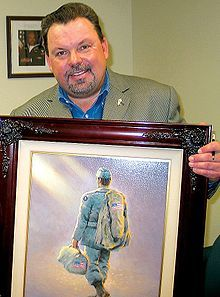 California artist THOMAS KINCADE,    'Painter of Light' (Jan 19, 1958 - April 6, 2012) was an American painter of popular realistic, bucolic, & idyllic subjects is pictured here with a copy of his painting  'Heading Home' presented to USO in Oct 2005. Kinkade, whose brushwork paintings of idyllic landscapes, cottages, lighthouses, & churches are enjoyed everywhere. He died at his home in Los Gatos, San Francisco Bay Area of natural causes Apr 6, 2012. (Apr 7, 2012)