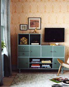 """Here, circular knobs, curvy feet, and two tones of sage-green paint evoke cool elegance. The open-and-closed construction showcases knickknacks and books while concealing electronics (and your shame-inducing """"O.C."""" box set)."""