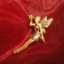 this pin is a gold tone fairy with pale orange stone in the star she is holding.. Never worn.! Measures 2 1/2 inches