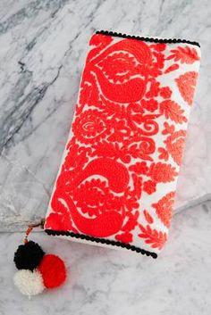 embroidered pom pom clutch