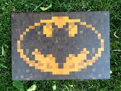 Pixelated Batman Bat Symbol Cutting Board.  Amazing craftsmanship. 8 pounds and 12x18x1.5 inches, this cutting board is made of yellow heart and walnut, assembled with waterproof food-safe wood glue, and coated with a mixture of mineral oil and beeswax. Other cutting boards available with either traditional or geeky motifs.