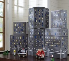 "These cool city building blocks are on sale for $50 at Pottery Barn.  Look close- they are really just screen printed cardboard boxes- to be mine for the low price of a couple tubes of paint from the $1 store! Gods""Lilla"" (my one year old)  is gonna have some fun tearing apart a city!"