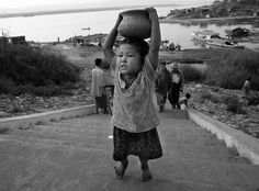 Paula Bronstein: A Burmese child struggles to carry a rice bowl on top of her head along the Ayeryarwady river February 23, 2007 in Mandalay, Myanmar (Burma). With economic sanctions crippling the Burmese economy it's people are eager for change and a better life. However, after the protest were squashed by the military regime's violent crackdown freedom is far from a reality and everyday life remains a serious struggle.