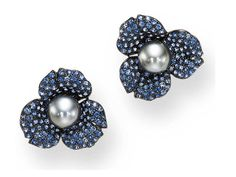 A PAIR OF SAPPHIRE AND GREY CULTURED PEARL EAR CLIPS, BY MIMI, BIJOUX ET OBJETS D'ART Each designed as a flowerhead centering upon a gray cultured pearl pistil measuring approximately 12.10 and 12.20 mm, extending pavé-set sapphire petals, mounted in oxidized 18K gold
